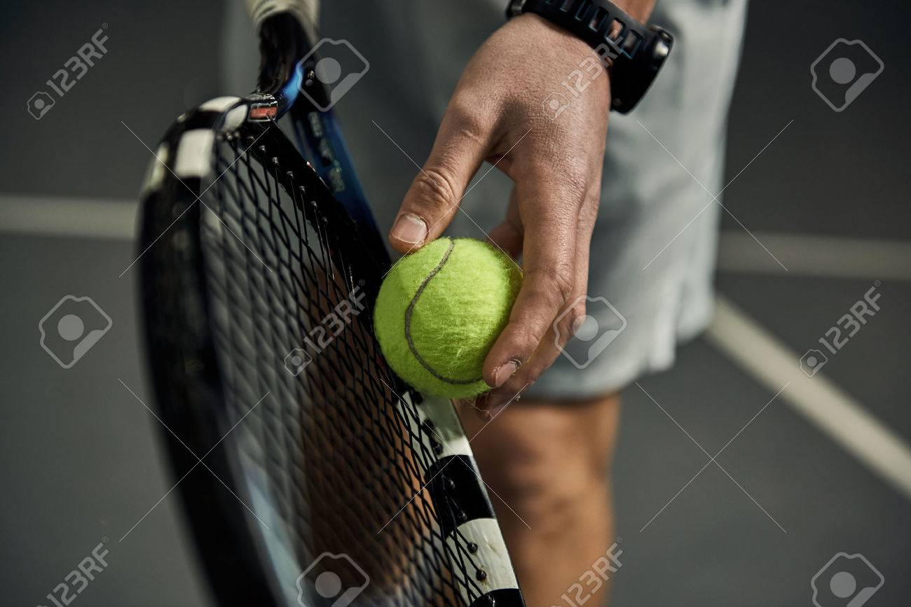 Close-up of male hand holding tennis ball and racket. Professional tennis player starting set. - 55392505