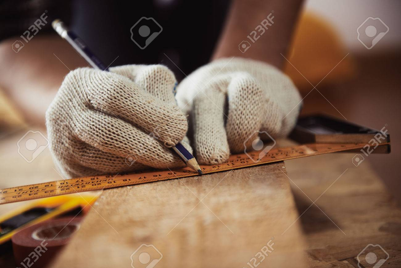Construction work. Woodwork. Male builder marking point on plank sitting on the floor. - 55392563