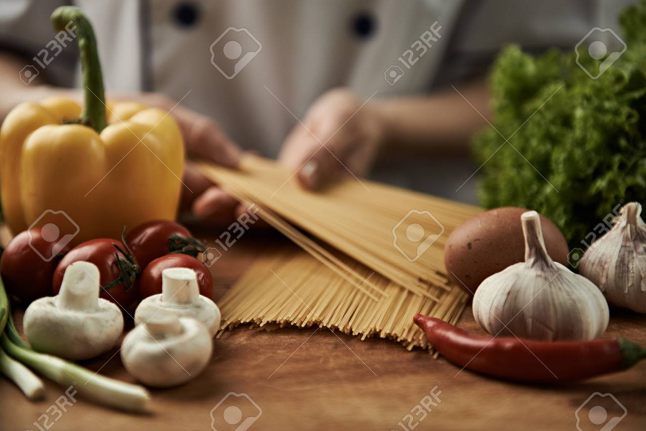 Woman chef cooking italian pasta with garlic, pepper, mushrooms, tomatoes and greens on wooden table. - 55392633