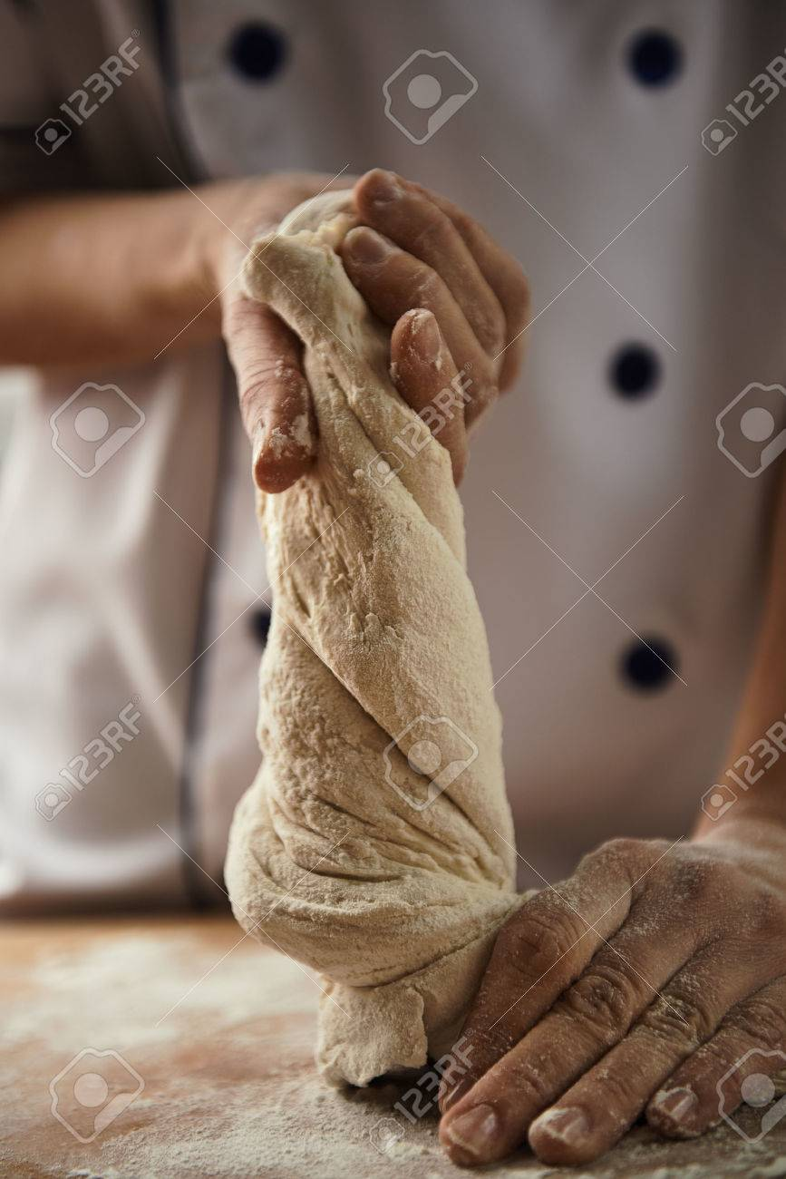 Close-up of female chef hands kneading the dough on the board. Bread preparation. - 55392650