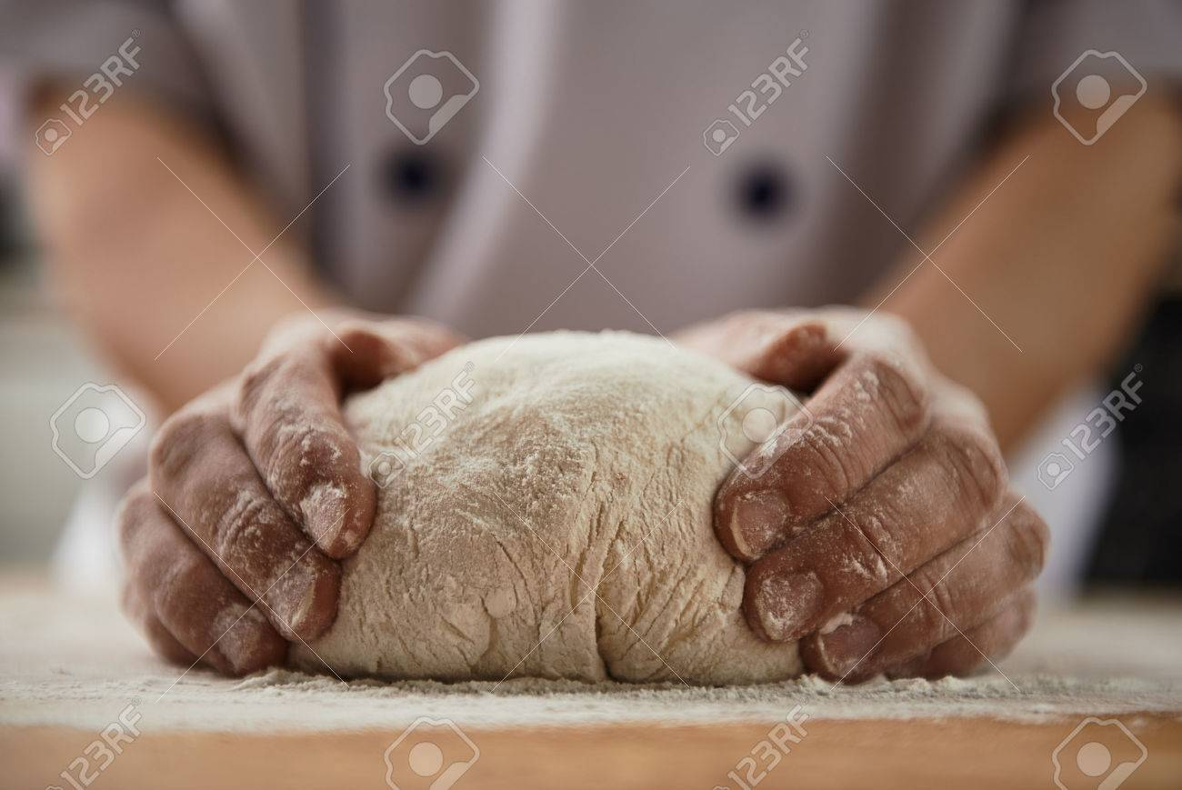 Close-up of woman baker hands kneading the dough on black board with flour powder. Concept of baking and patisserie. - 55392653
