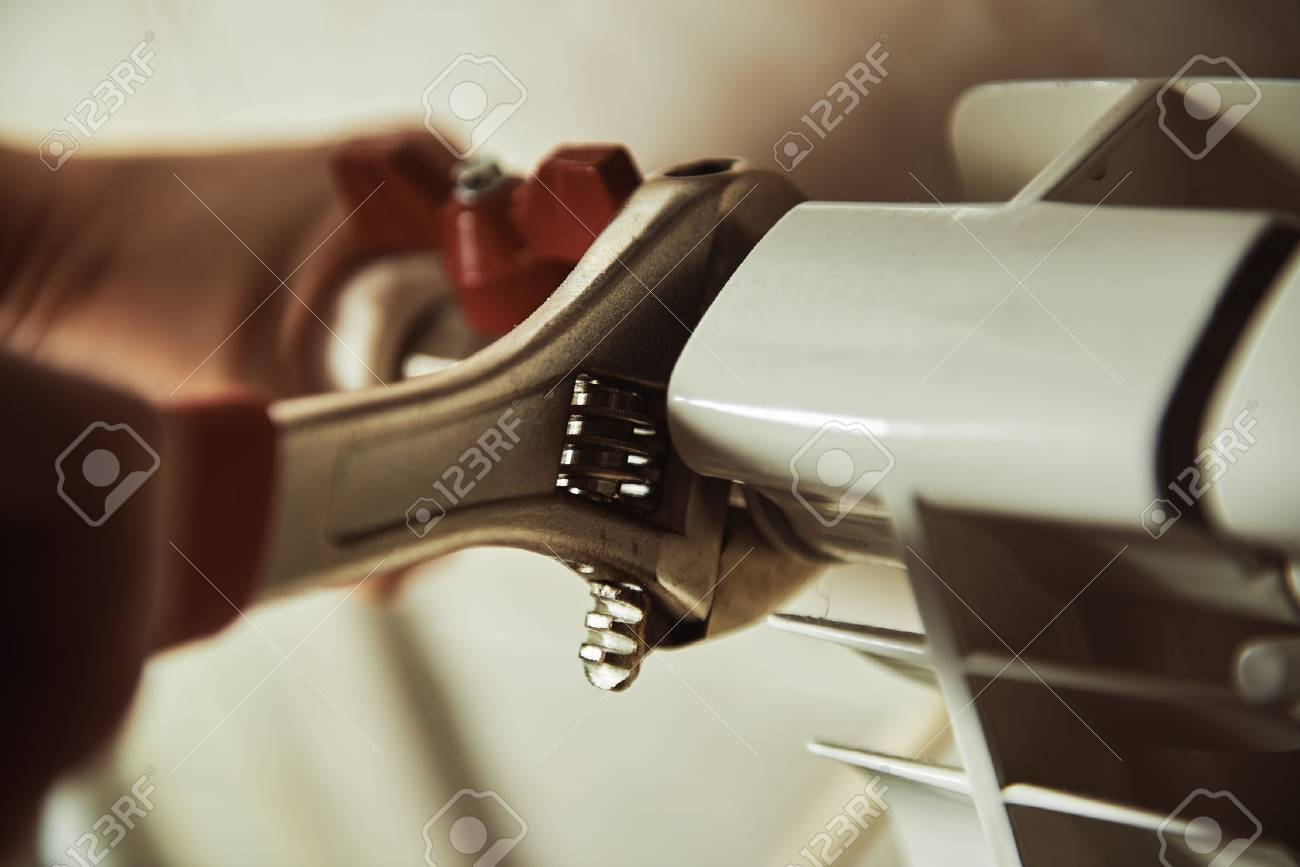 Close-up of technician hands checking radiator and heating in a house. Concept of heater repair. - 55392673