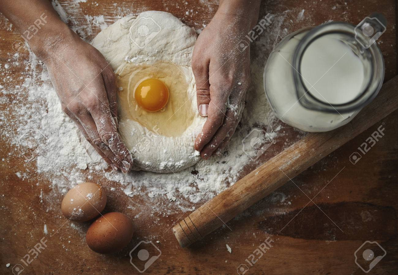 Closeup of female hands mixing dough with egg and flour on wooden board in rustic kitchen. - 55392696
