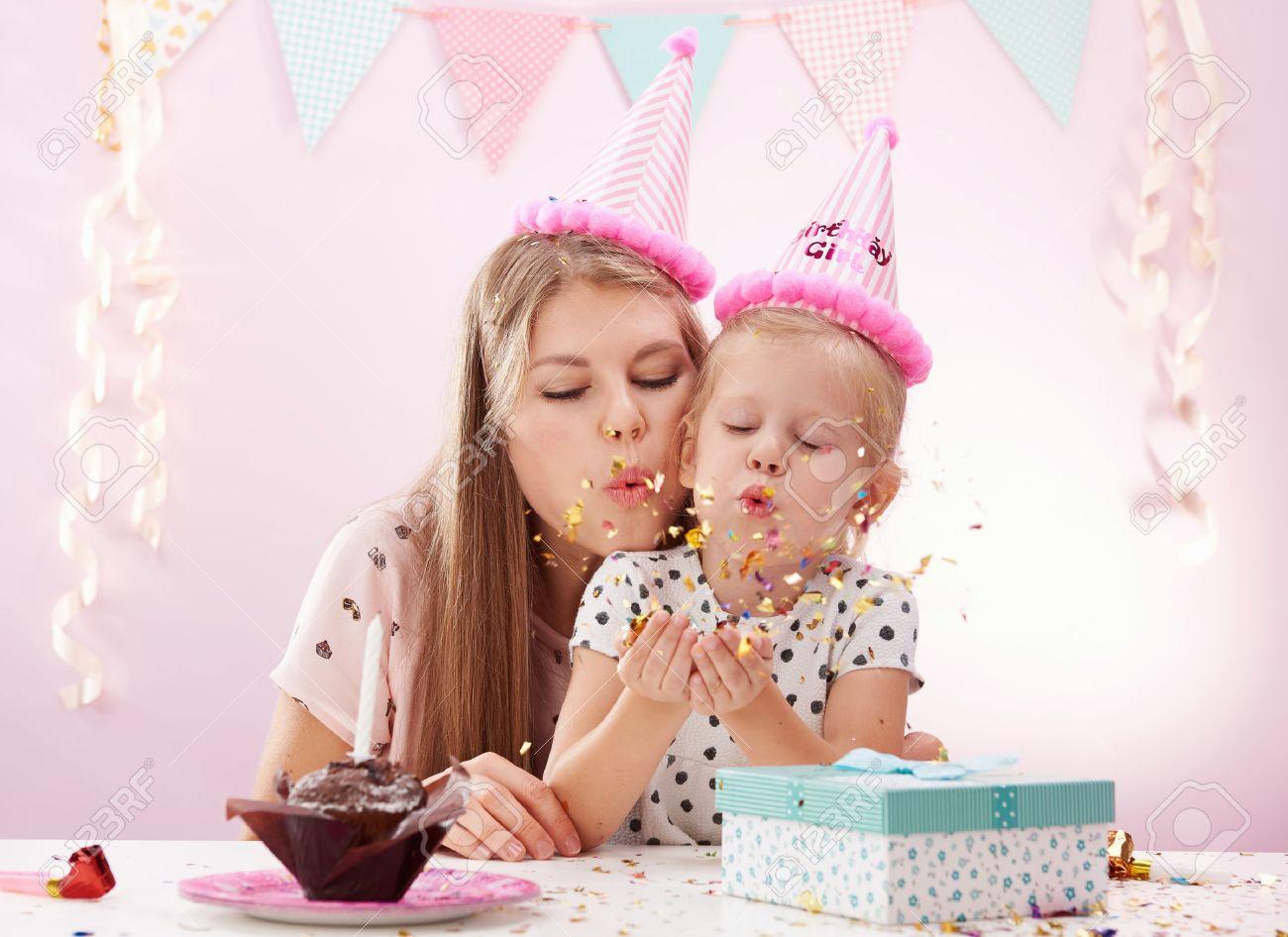 Retrato De Madre E Hija Que Sopla Confeti De Oro Que Celebran