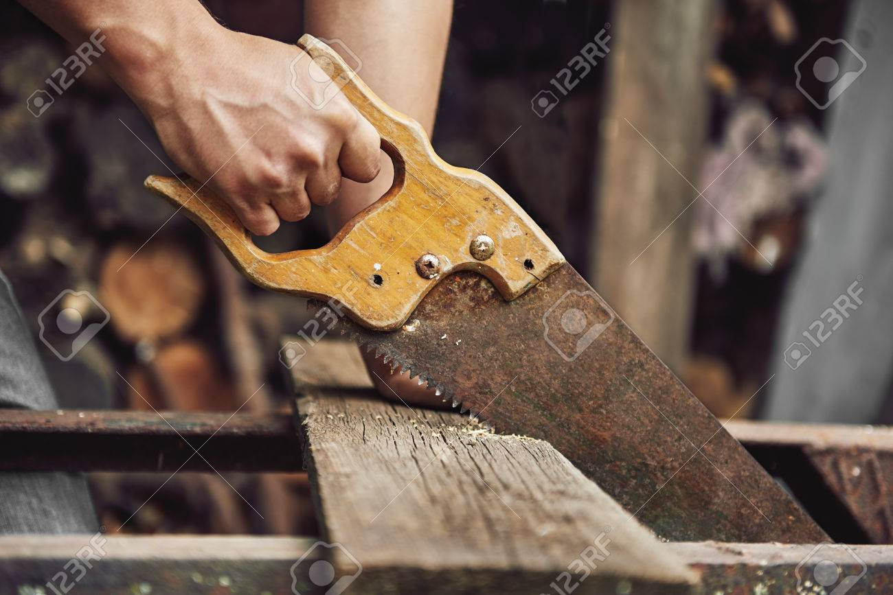 Carpenter With Handsaw Cutting Wooden Board In Workshop Concept