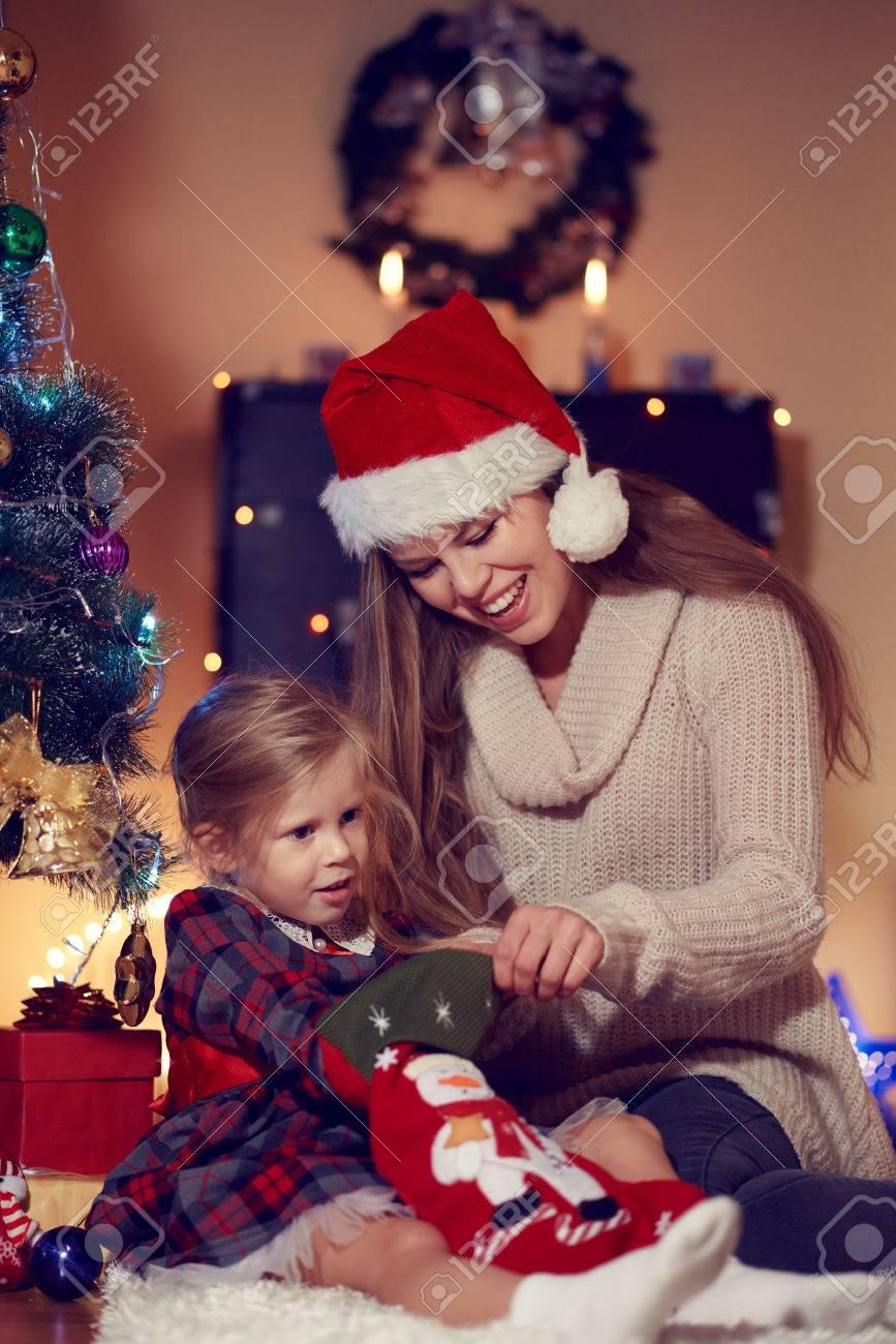f44cb4c276aa6 Cute Petite Fille En Robe De Fête Assis Sur Le Sol Avec La Maman De Prendre  Des Bonbons De Noël Chaussette. Famille Nouveau Tradition De L'année Et Le  ...