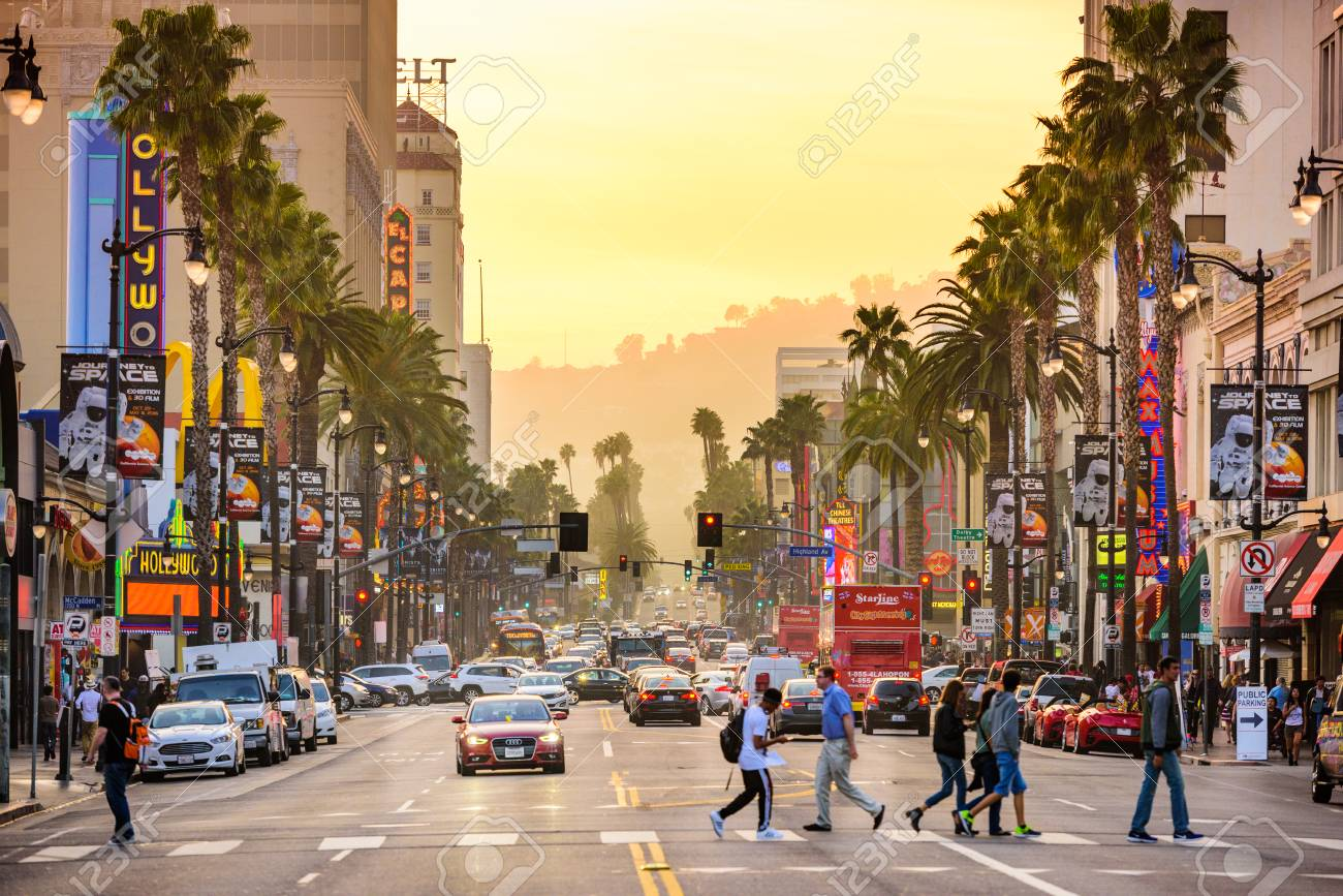 LOS ANGELES, CALIFORNIA - MARCH 1, 2016: Traffic and pedestrians on Hollywood Boulevard at dusk. The theater district is famous tourist attraction. - 59300470