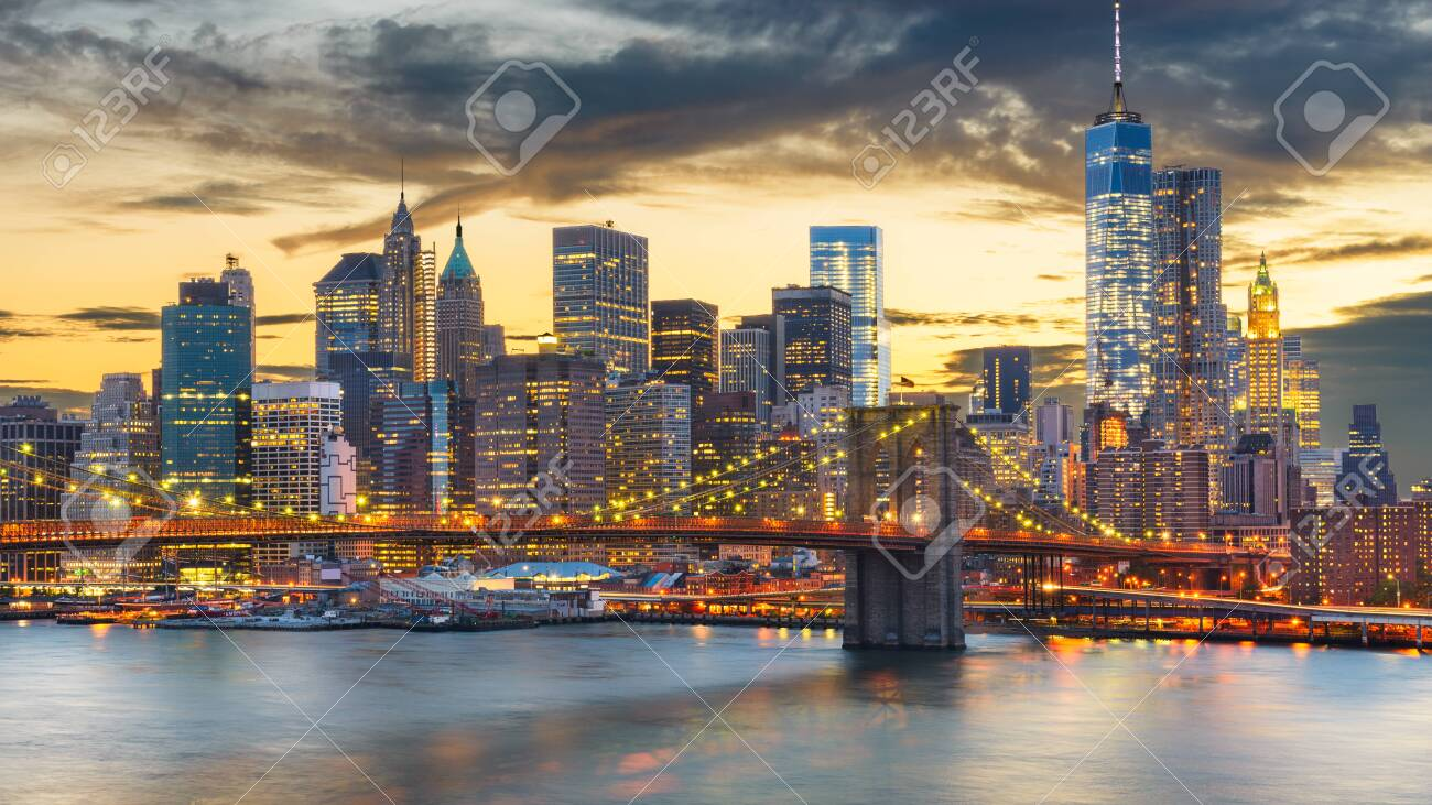 New York, New York, USA downtown Manhattan city skyline over the East River with the Brooklyn Bridge at dusk. - 135508685