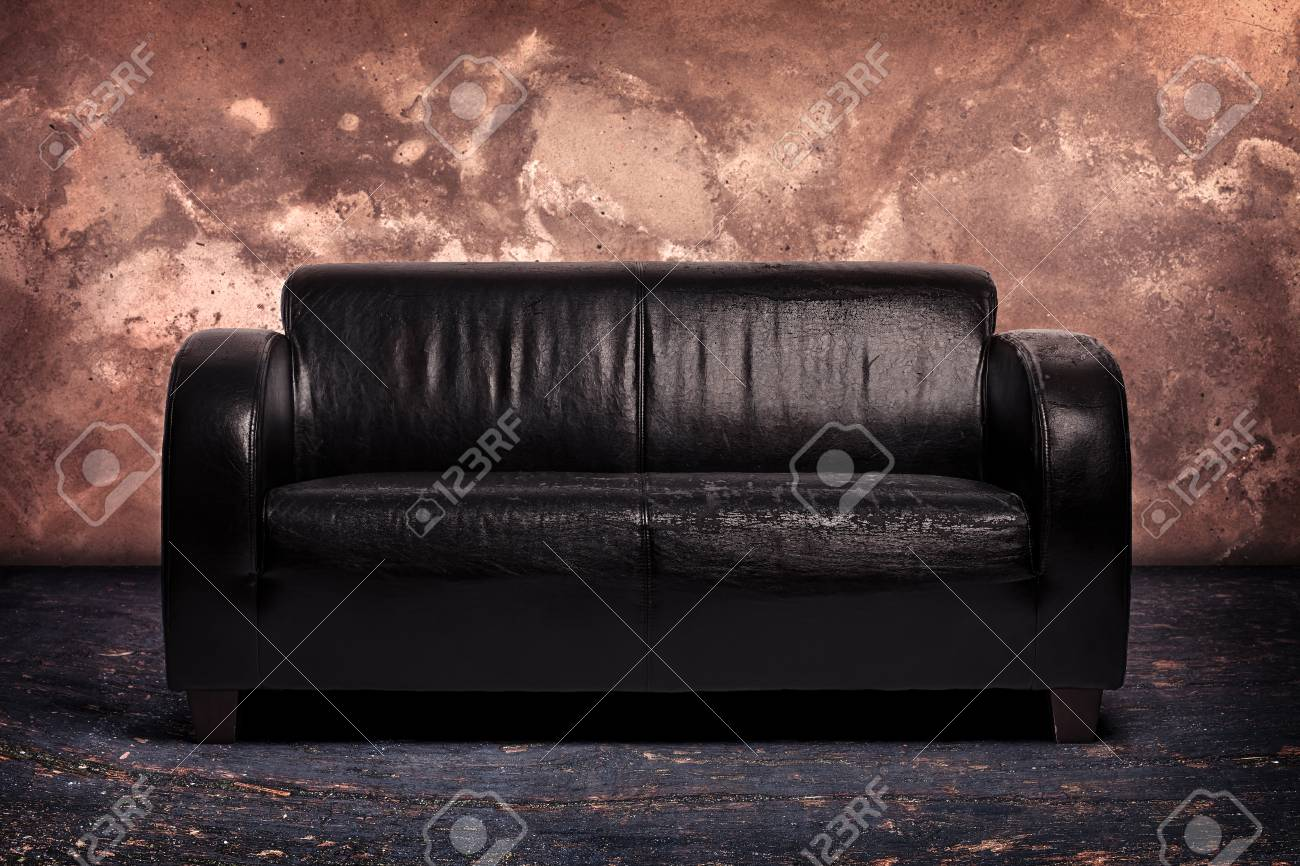 Old leather couch on sandstone background