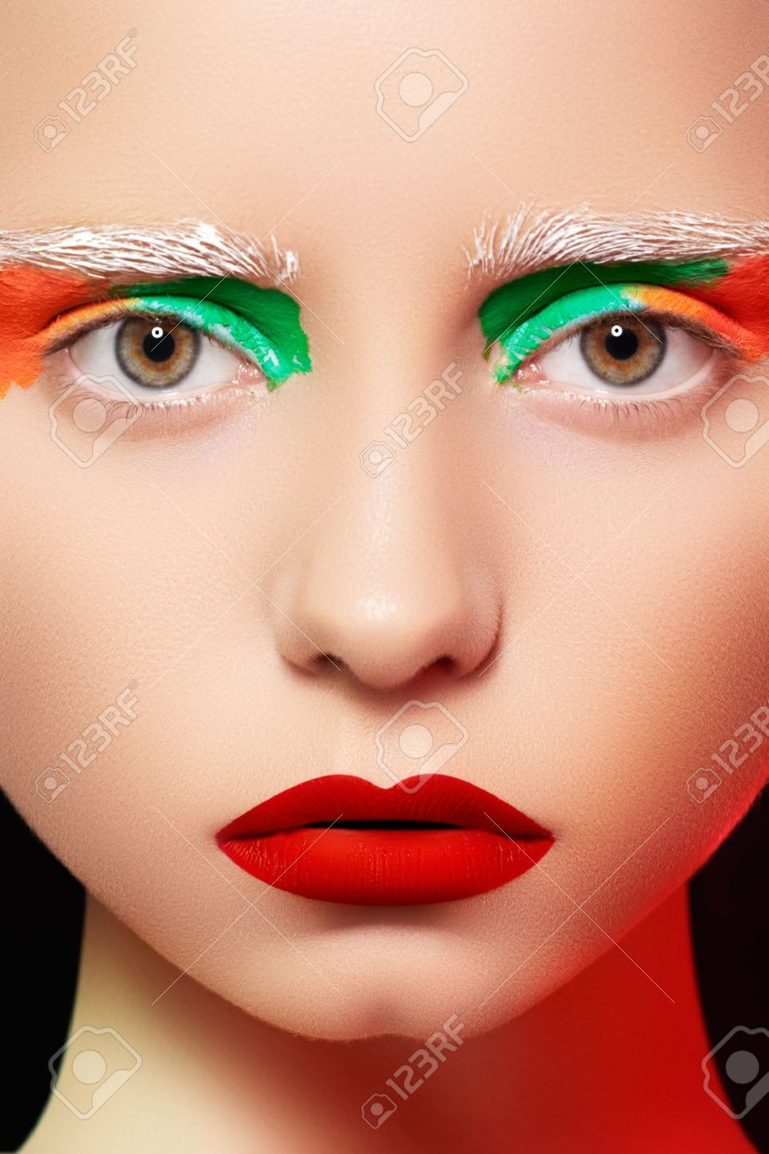 High fashion and beauty portrait photography. Beautiful girl model face with creative bright makeup like