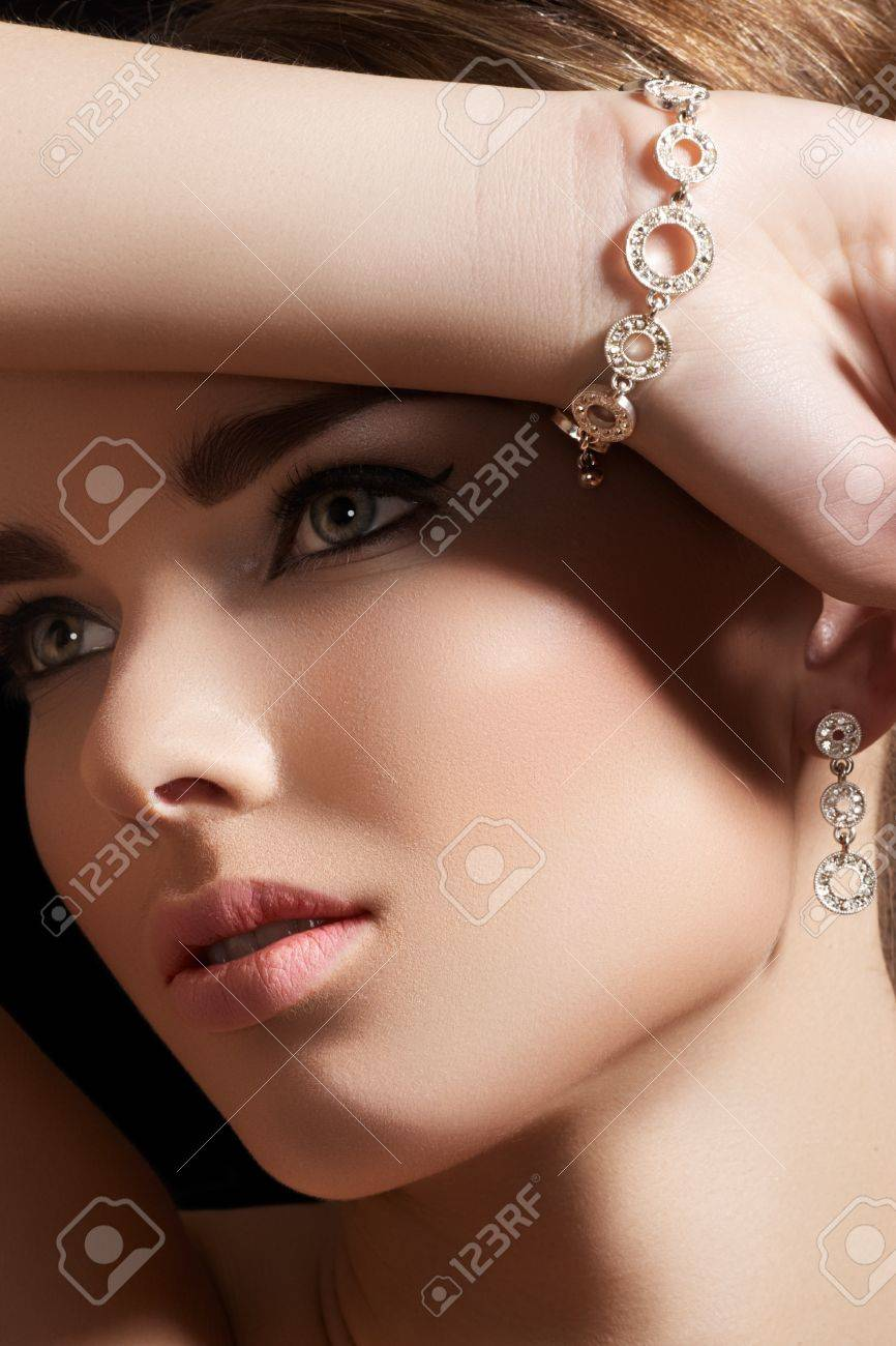 Beautiful woman model in retro style make-up. Accessories, jewelry gold bracelet and earrings with diamonds. Chic makeup and luxury jewellery Stock Photo - 11714067