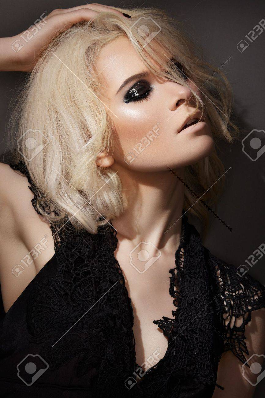 Evening and night style. Beautiful blond woman model in lacy black dress, with dark gloss make-up Stock Photo - 11714073