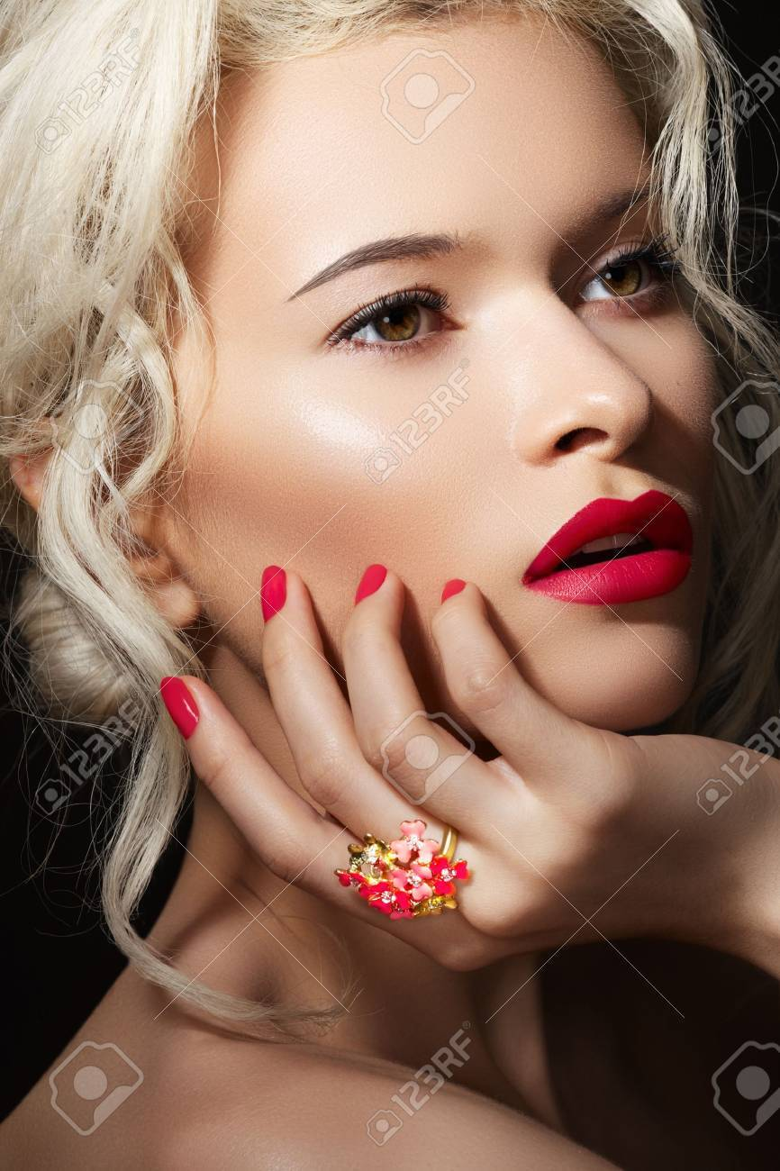 Wellness, cosmetics and romantic retro style. Close-up portrait of sensuality beautiful blond woman model face with fashion make-up, sexy evening red lips makeup and bright red manicure Stock Photo - 11713842