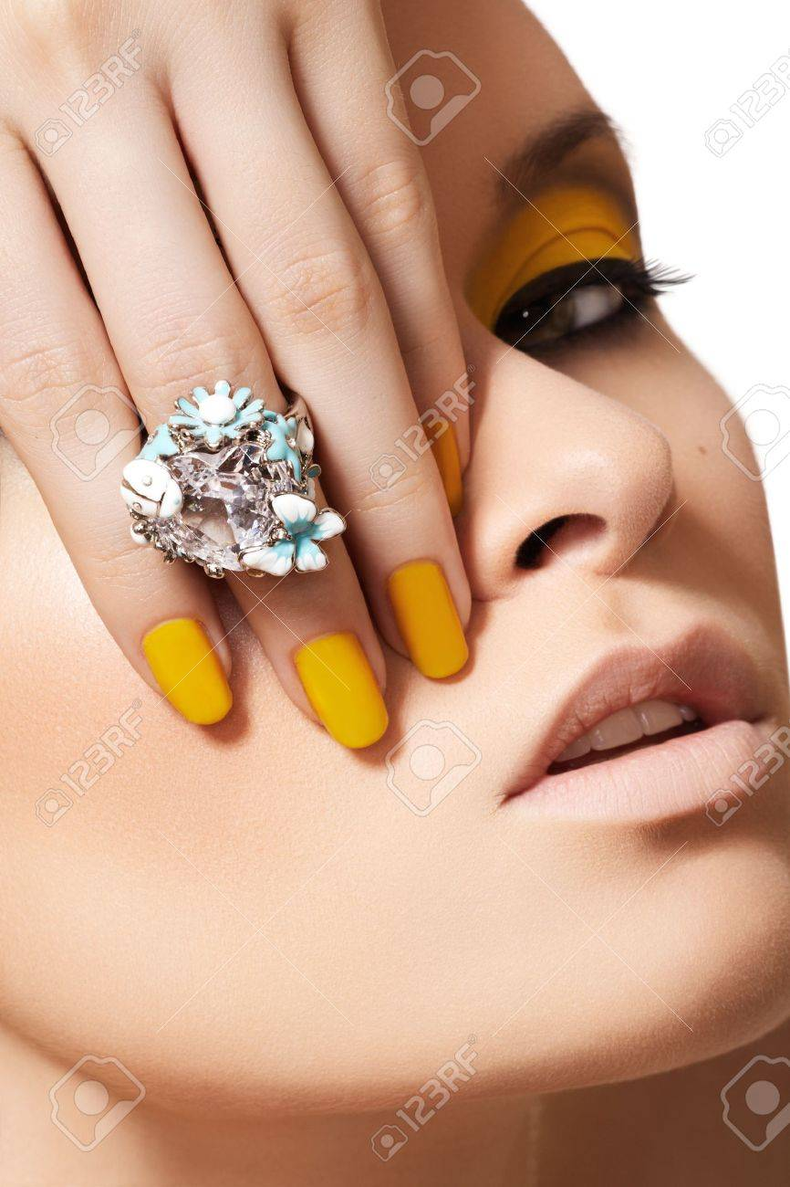 Close-up portrait of beautiful model face with neon yellow fashion make-up and with big crystal ring. Disco makeup and manicure, bright nail polish Stock Photo - 11713832