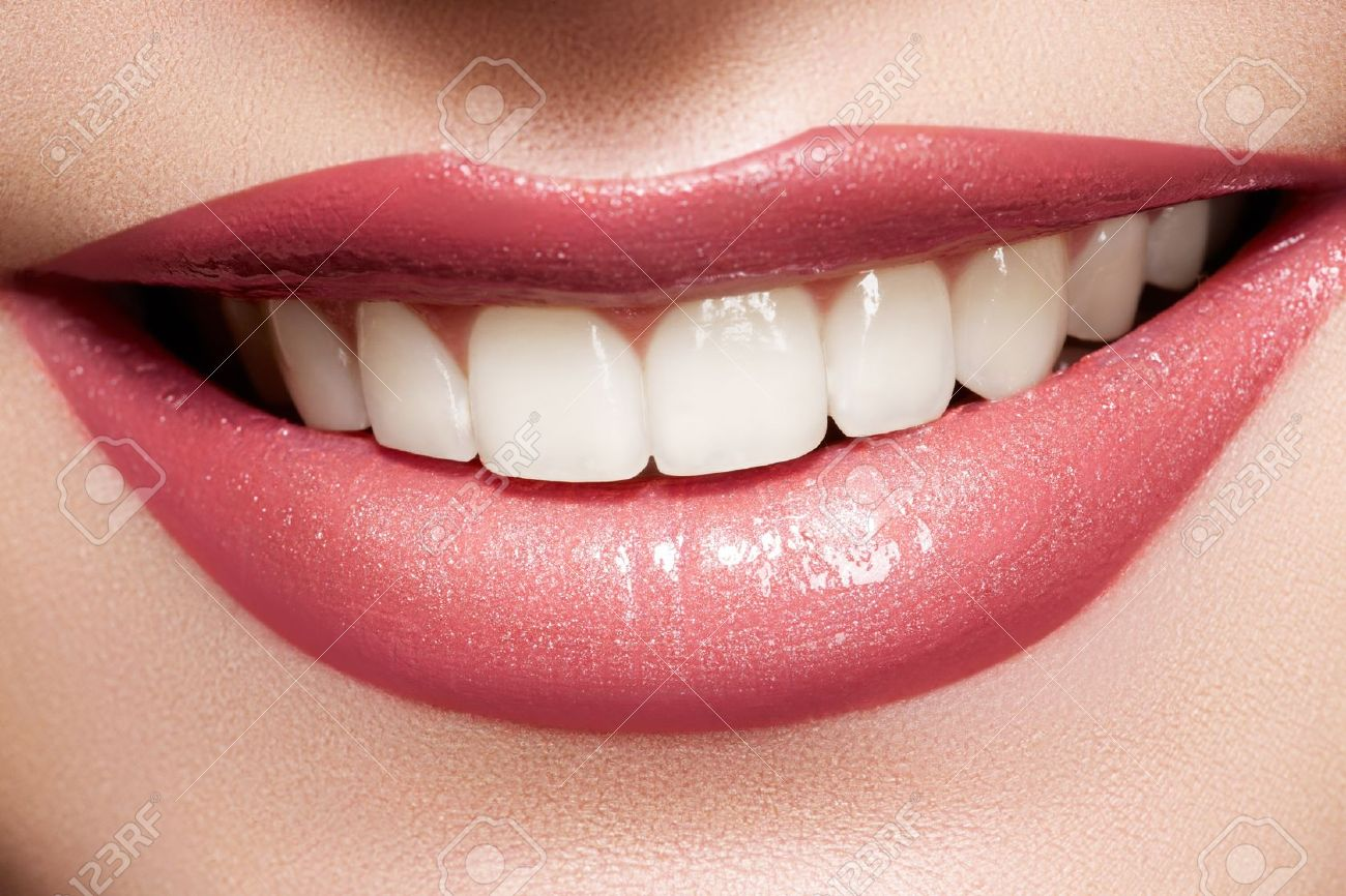 Close-up happy female smile with healthy white teeth, bright gloss lips make-up. Cosmetology, dental and beauty care - 11572500