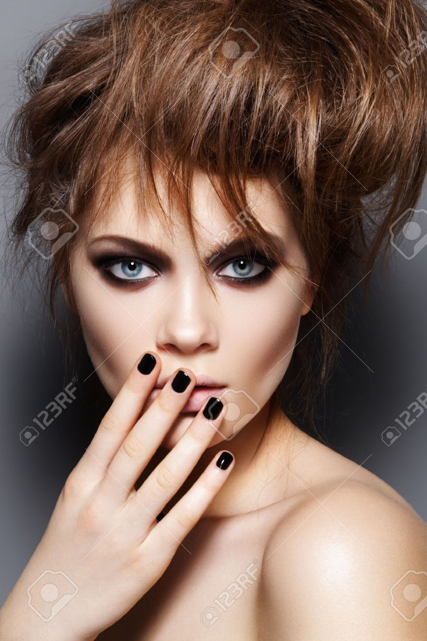 Fashion model with tousled hair, make-up, manicure. Portrait of young fashion woman with punk rock hairstyle, dark make-up, black nail polish Stock Photo - 11540692