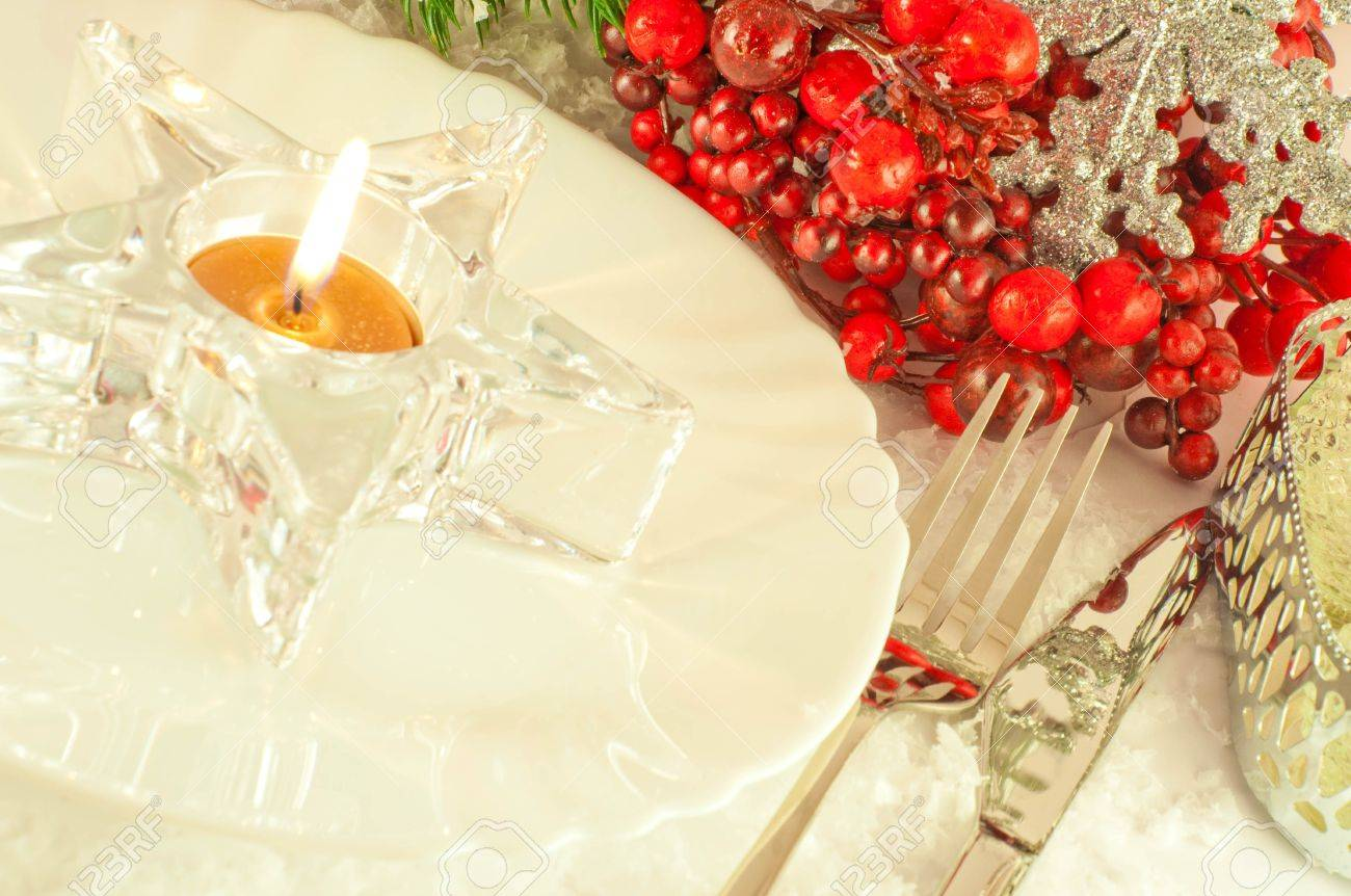 Christmas table layout, candlestick in the form of a star with a branch of berries Stock Photo - 11377124