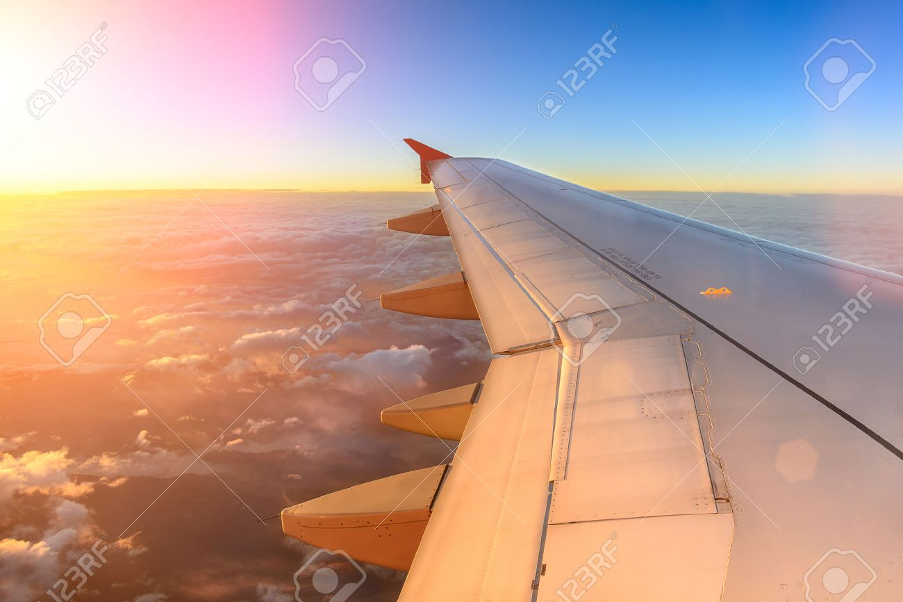 Aerial view of airplane flying above shade clouds and sky from an airplane fly during the sunset. View from the plane window of emotional moment during international travel around the world. - 53797283