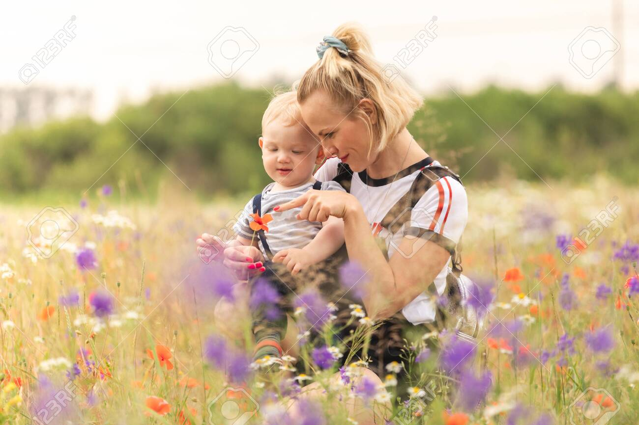 Mother and child playing in the field with flowers. - 122886205