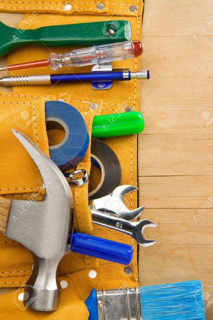 tools and instruments in leathern belt on wooden texture - 22295251
