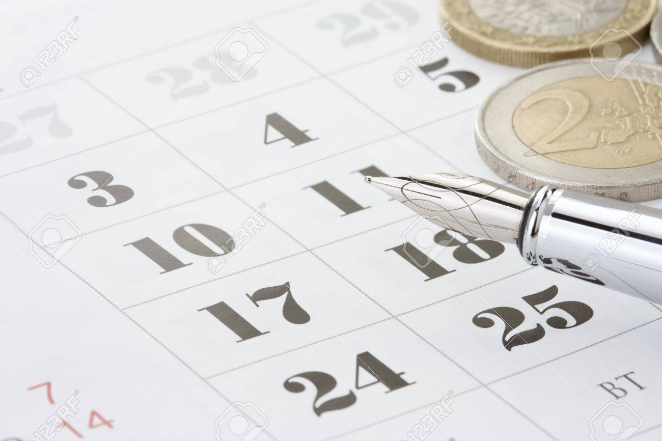 ink pen and coin money on calendar background Stock Photo - 15087293