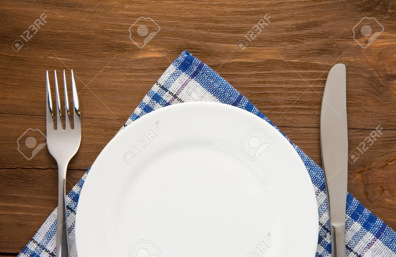 white plate, knife and fork at napkin on wooden background Stock Photo - 20103575