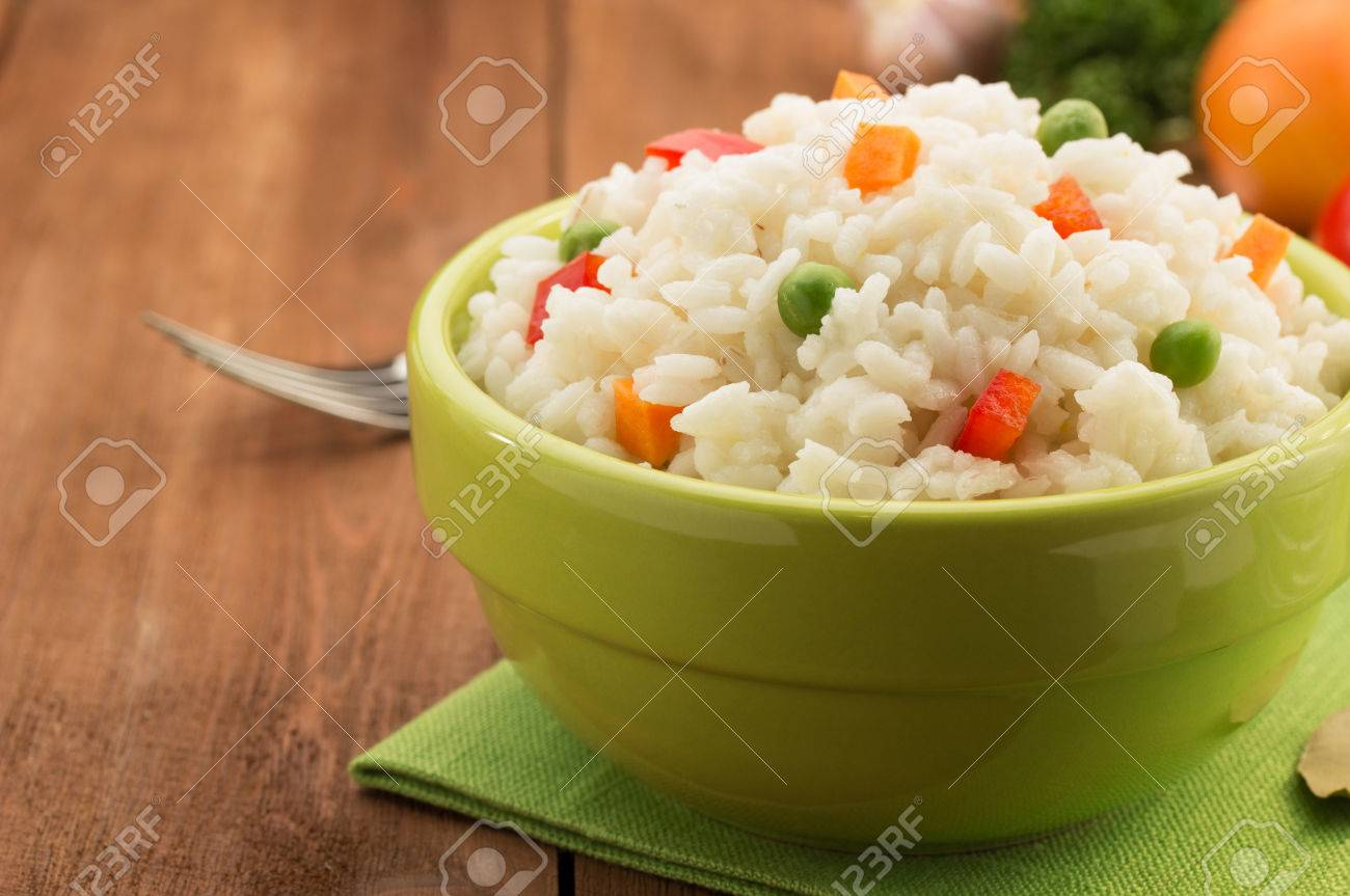 bowl full of rice isolated on wooden background - 37299482