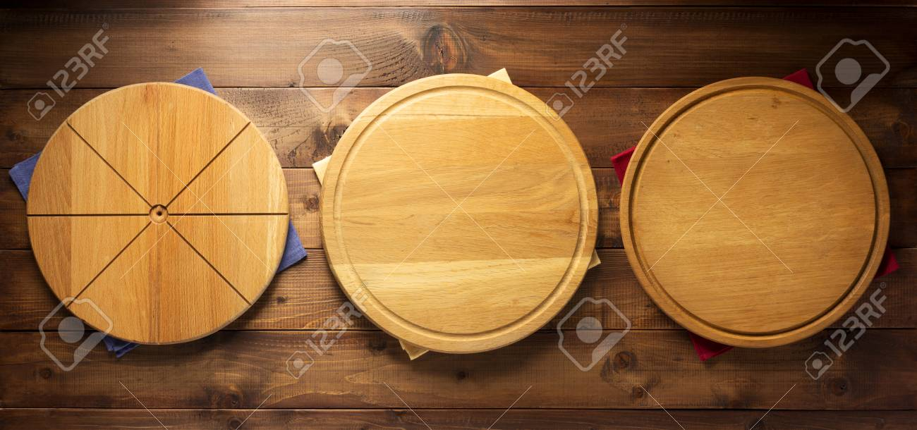 pizza cutting board and napkin cloth at wooden table, top view