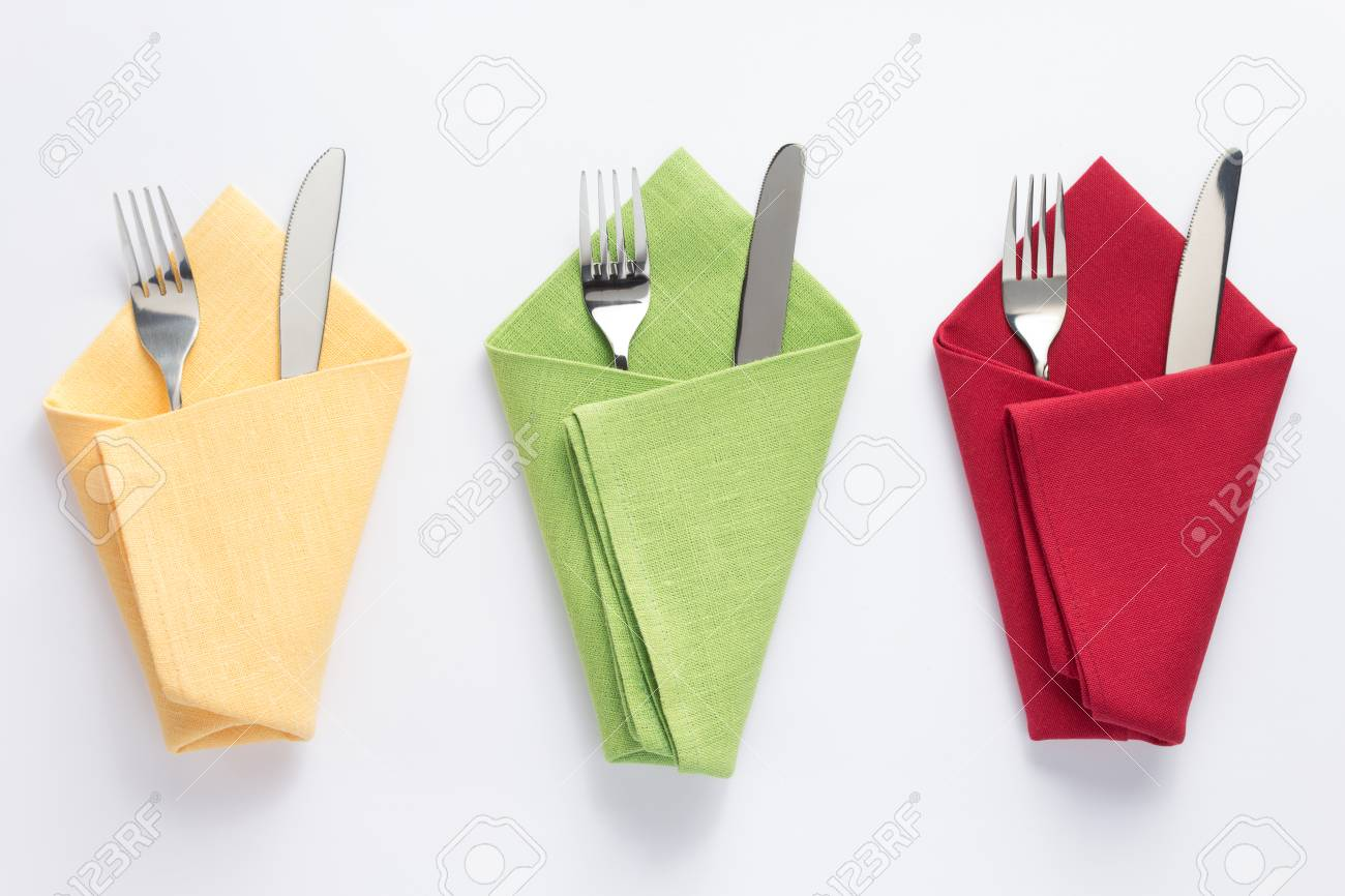 knife and fork in folded napkin at white background, top view - 112337659