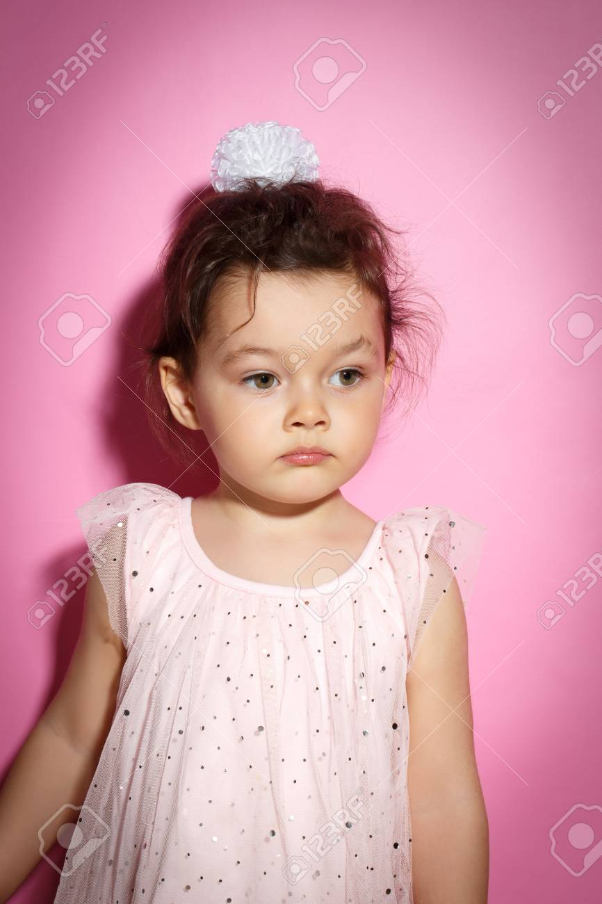 31a0d791deba Portrait of Sad 3 year old little girl with dress, on bright pink  background Stock