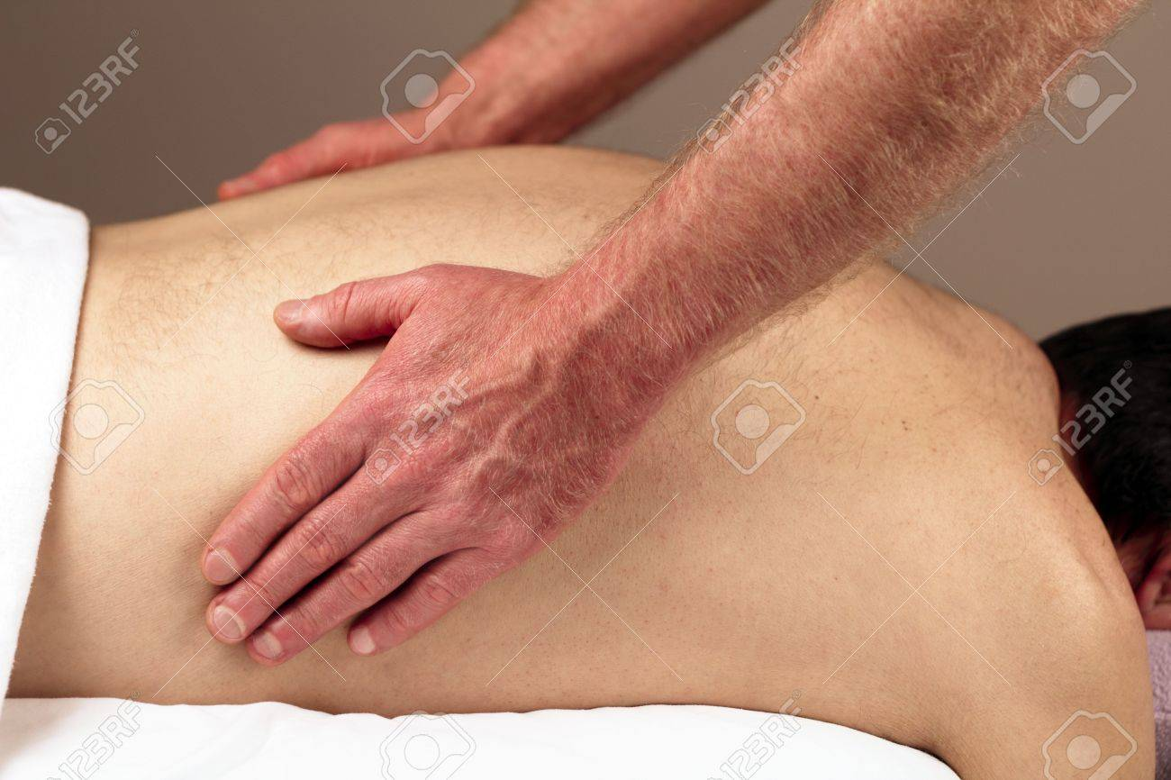 Male receiving a massage therapy from a male massage therapist. Stock Photo - 8169359