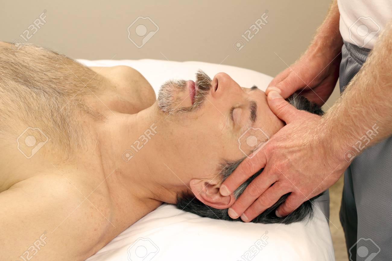 Mature guy receiving a relaxing facial massage from a masseur at a day spa. Stock Photo - 8169358