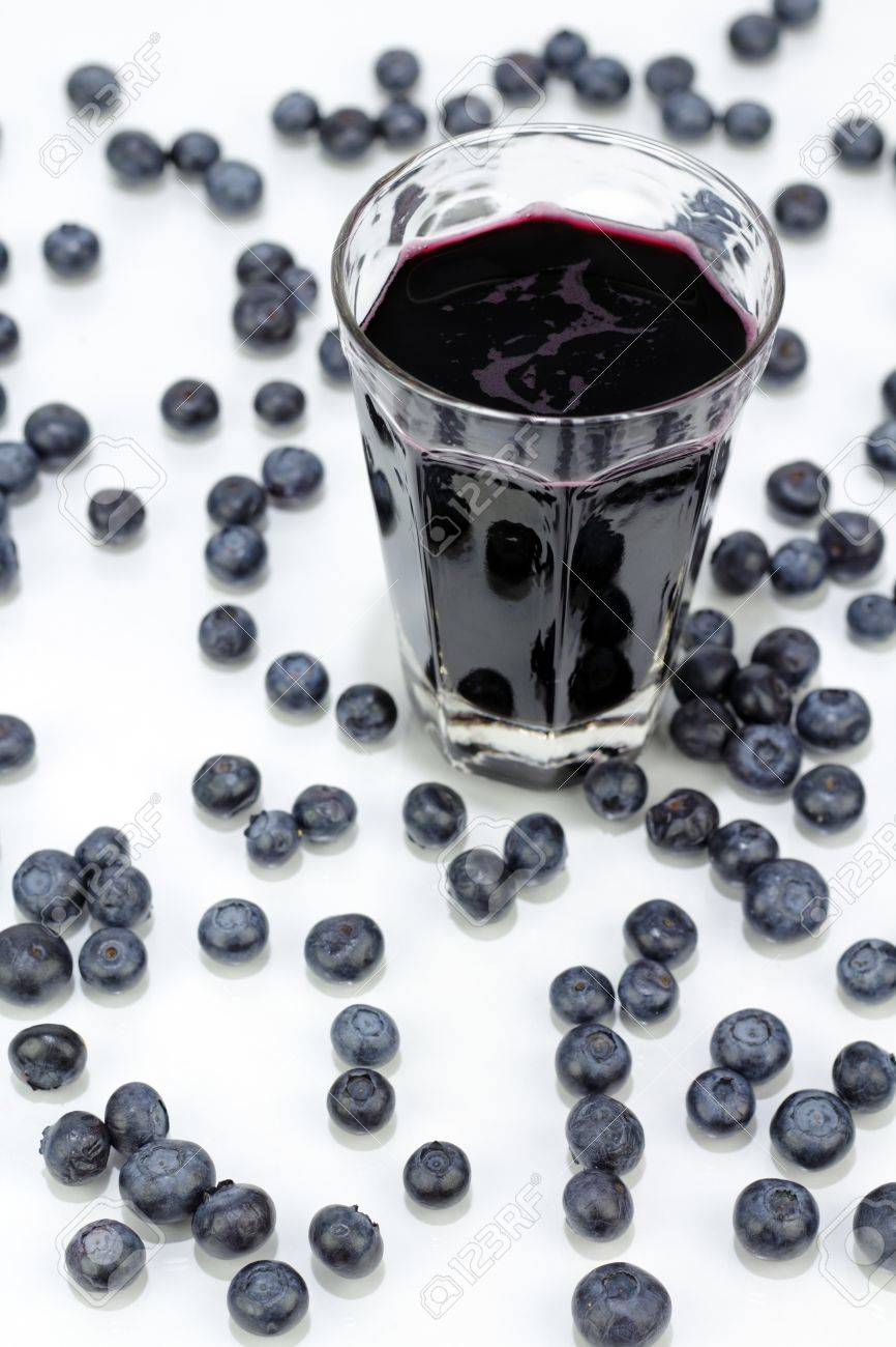 Deep purple berry juice in clear glass, whole fruit abstract on white reflective surface. Stock Photo - 8627245