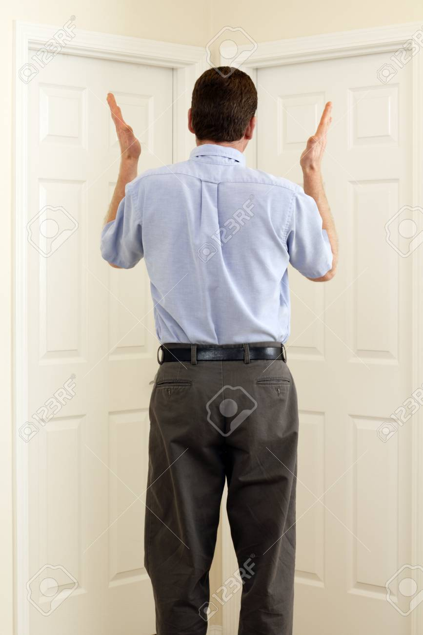 Man between two doors with hands in the air not sure which to choose. Stock Photo - 8921565