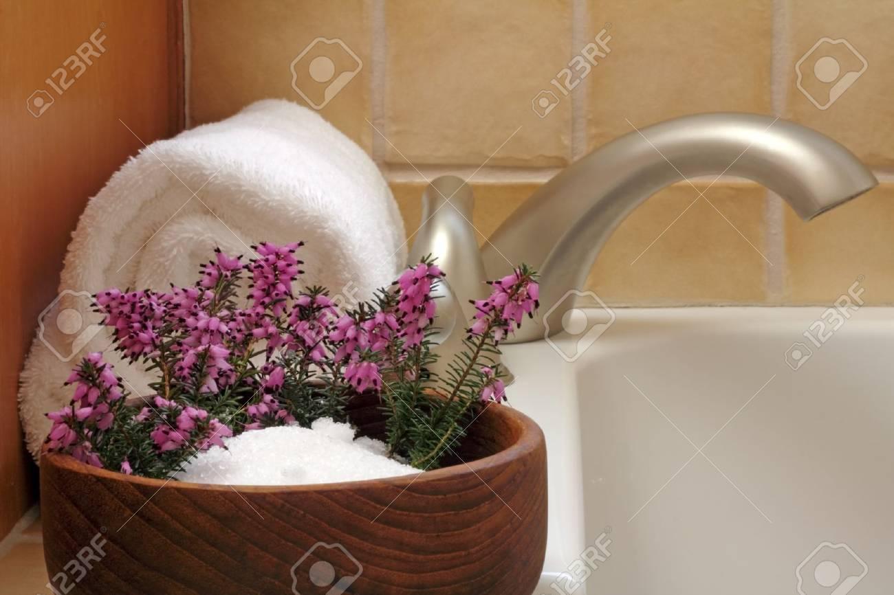 Epsom salts in a teak wood bowl with purple heather flowers and white bath towel on edge of a modern bath tub. - 8994809