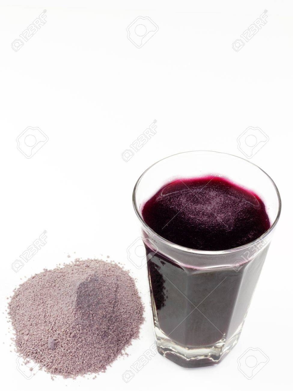 Violet purple dried and ground extract mix of berries and similar with a glass of the beverage made with water. Stock Photo - 9506763