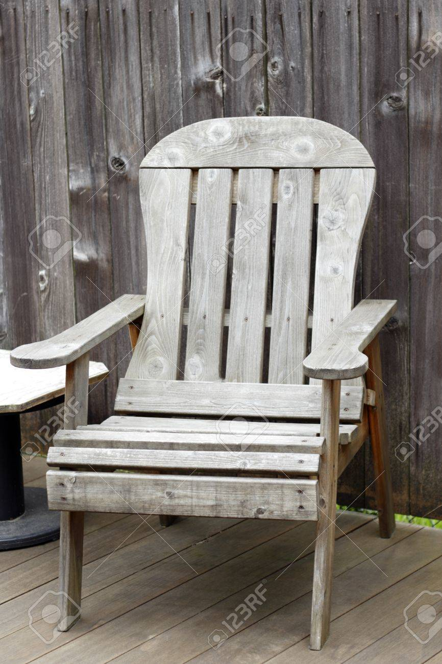 Old Wood Patio Chair On An Outside Backyard Deck With A Weathered Wood  Fence Behind It