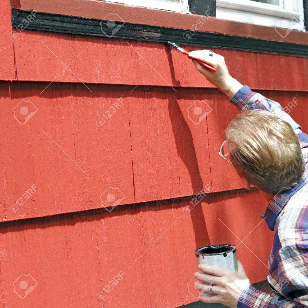 Man painting house window trim with black paint. Stock Photo - 9566365