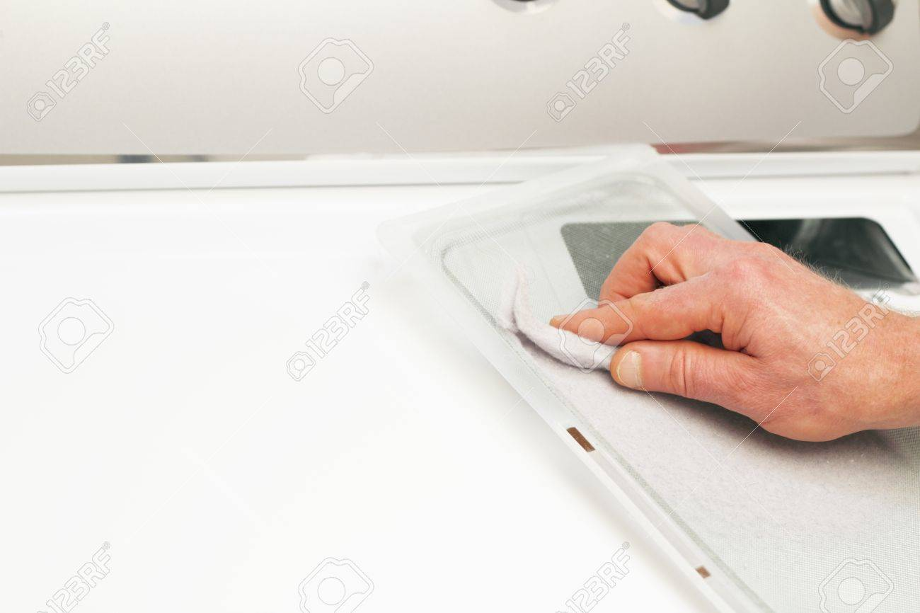 Male hand cleaning the clothes dryer dirt collector of excess dust and fibers. Stock Photo - 9566369