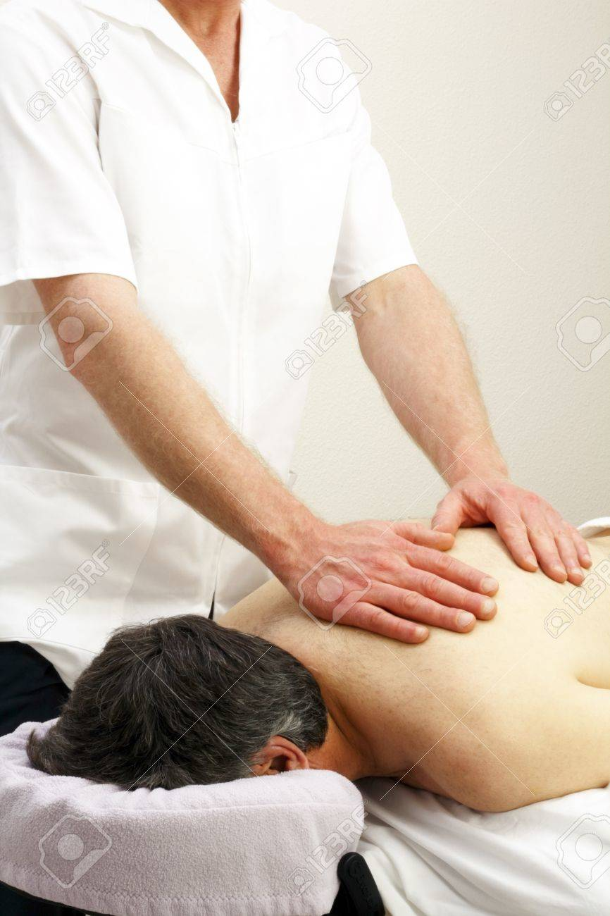 Male laying face down getting an upper torso massage from a professional male massage therapist. Stock Photo - 9746004