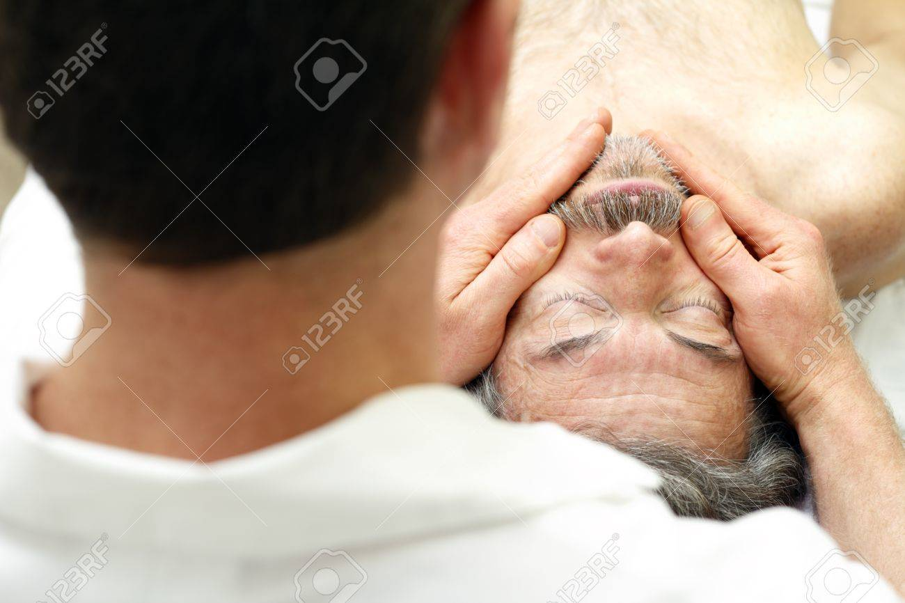 Mature man getting face massaged by a male massage therapist at a healthy spa. Stock Photo - 9746001