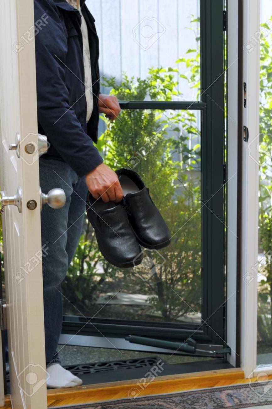 Man seen below shoulders entering front door with shoes in hand. Stock Photo - 9744590