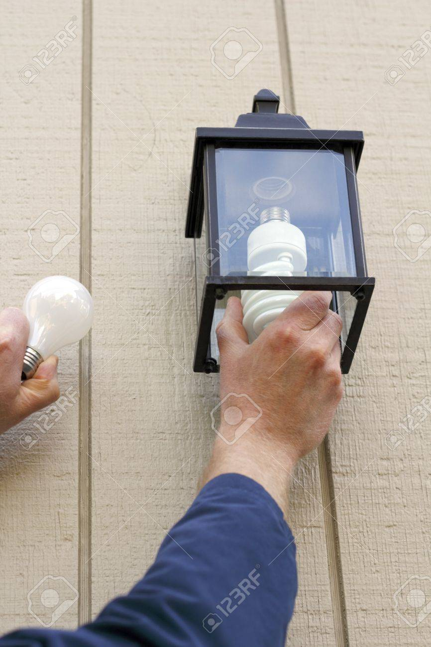 Man carefully replacing an old incandescent lightbulb with a new CFL light in an outdoor fixture to save money when the lamp is on. Stock Photo - 9744675