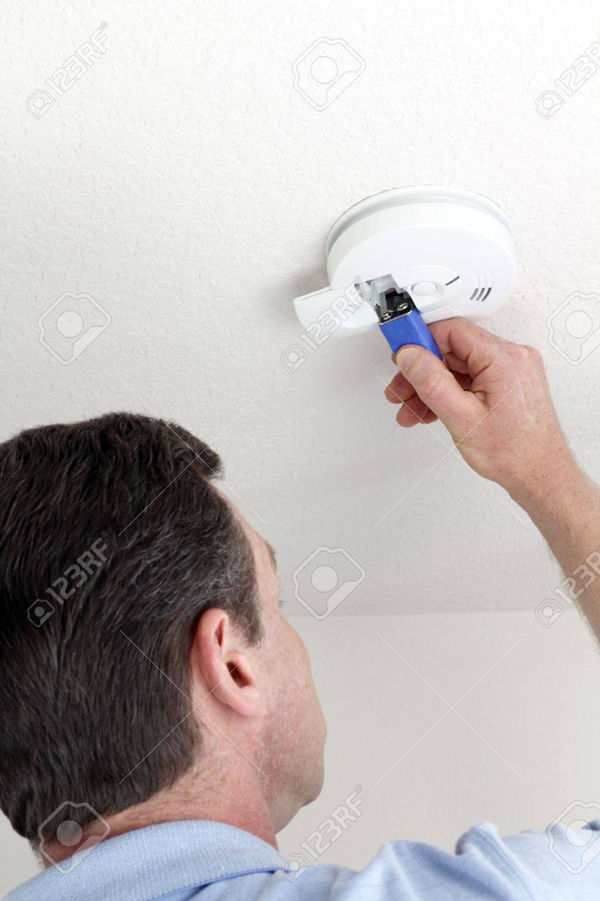 Man carefully replacing 9 volt battery in round white ceiling smoke alarm detector for the safety of his household. Stock Photo - 9884322