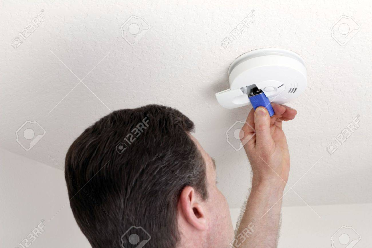 Man changing the 9 volt battery in a round white ceiling smoke alarm detector for fire safety. Stock Photo - 9884324