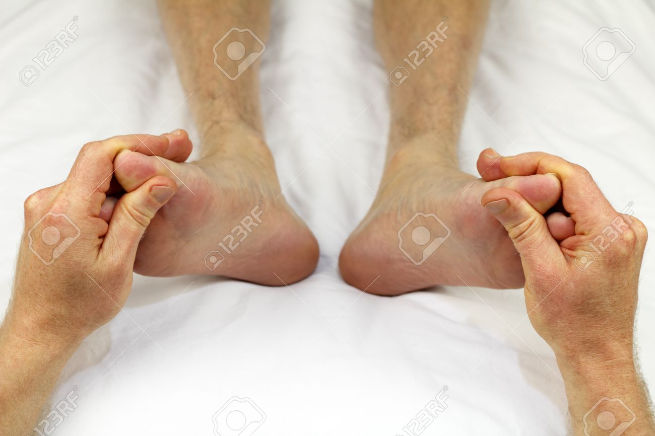 Big toes of both feet of an adult male receiving massage from a reflexologist as part of a treatment to promote circulation. Stock Photo - 9884325