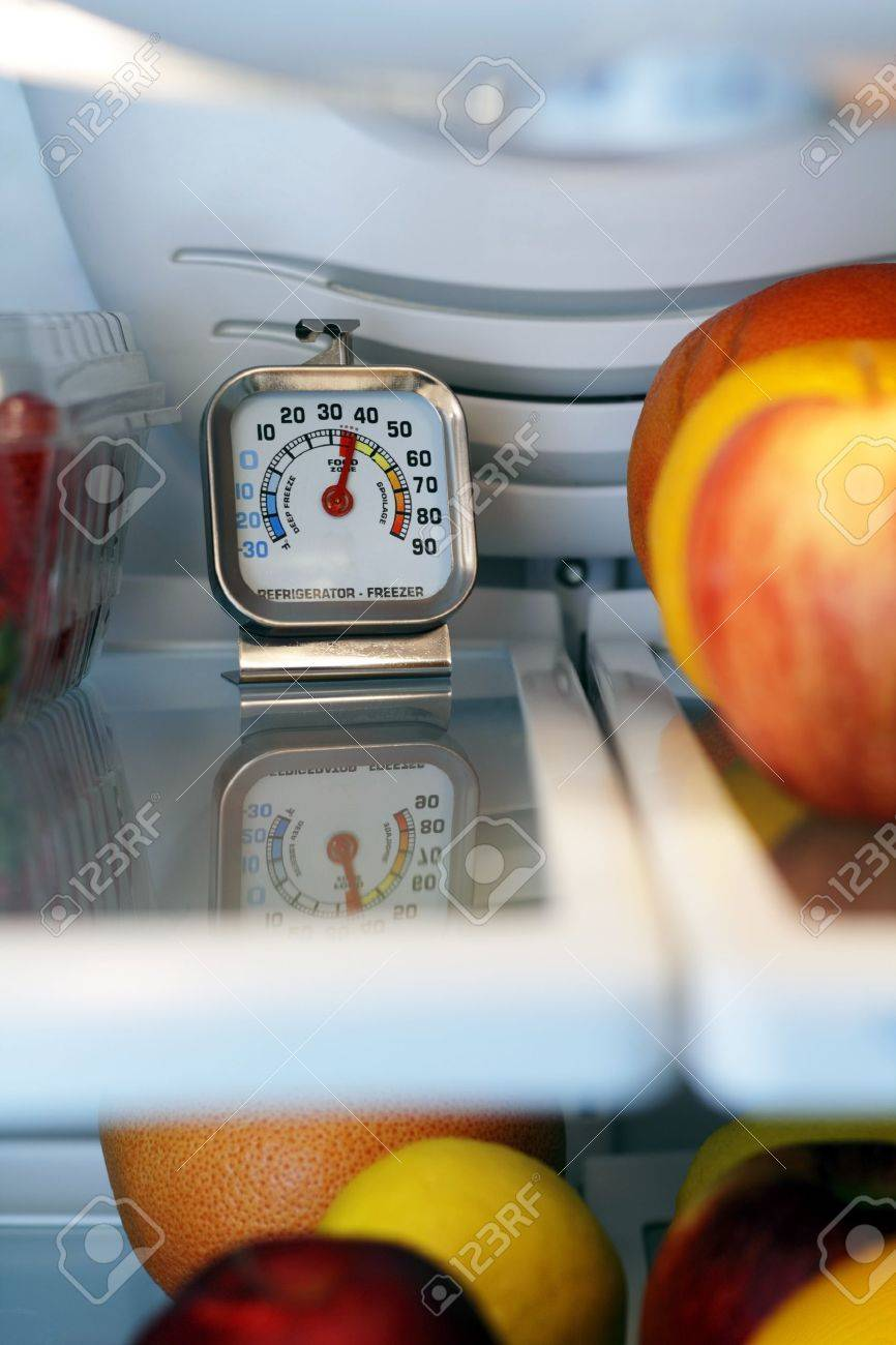 Refrigerator freezer temperature thermometer inside the top shelf of a cool food storage fridge to make sure perishables are kept safe and not too warm. Stock Photo - 9884390