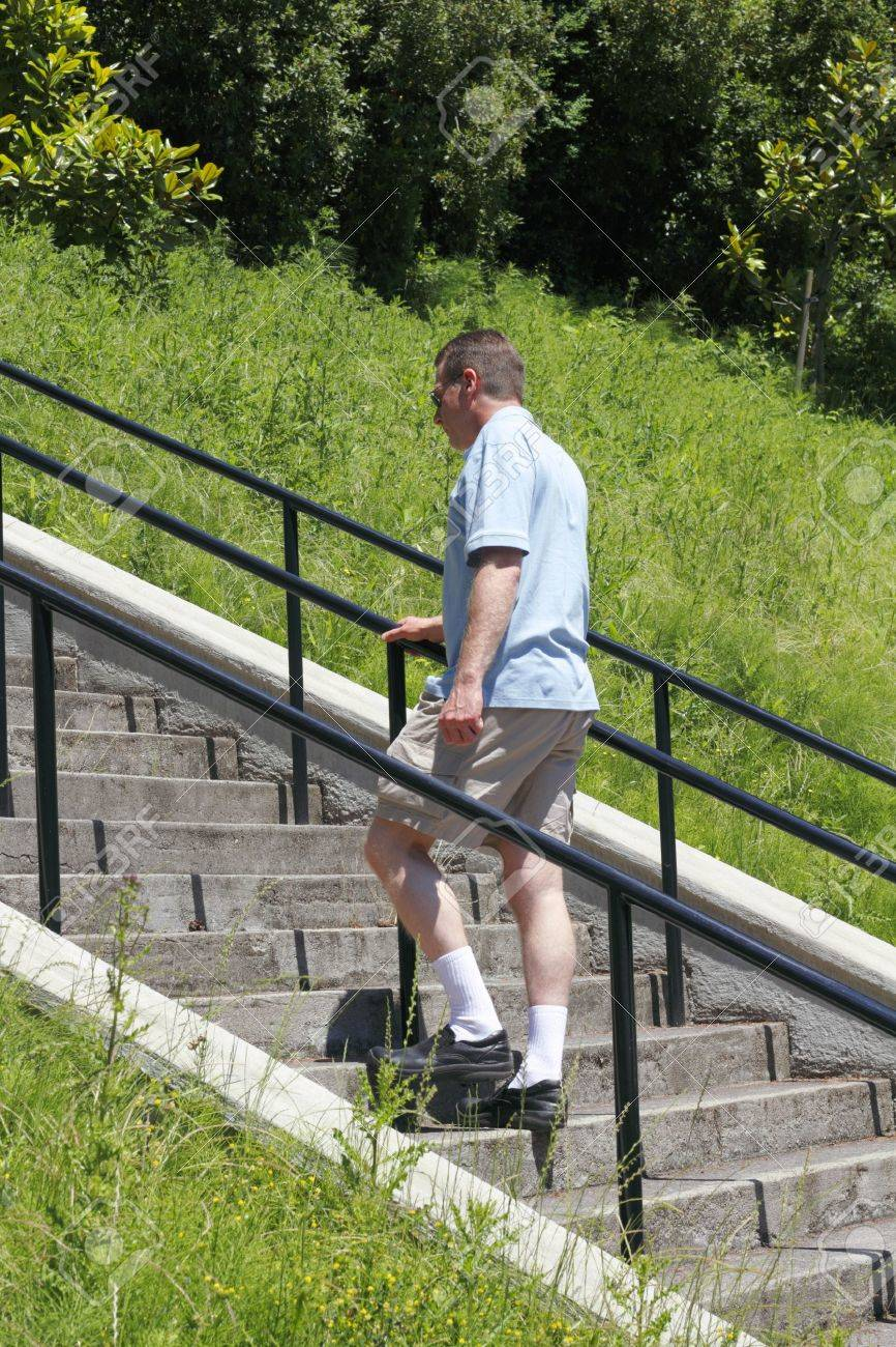 Man walking up stairs outside surrounded by landscape on a sunny summer day. Stock Photo - 10328314