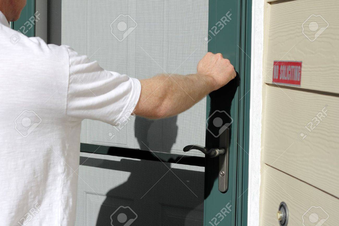 Man knocking on the front door of a home on a sunny day. Stock Photo - 10740155