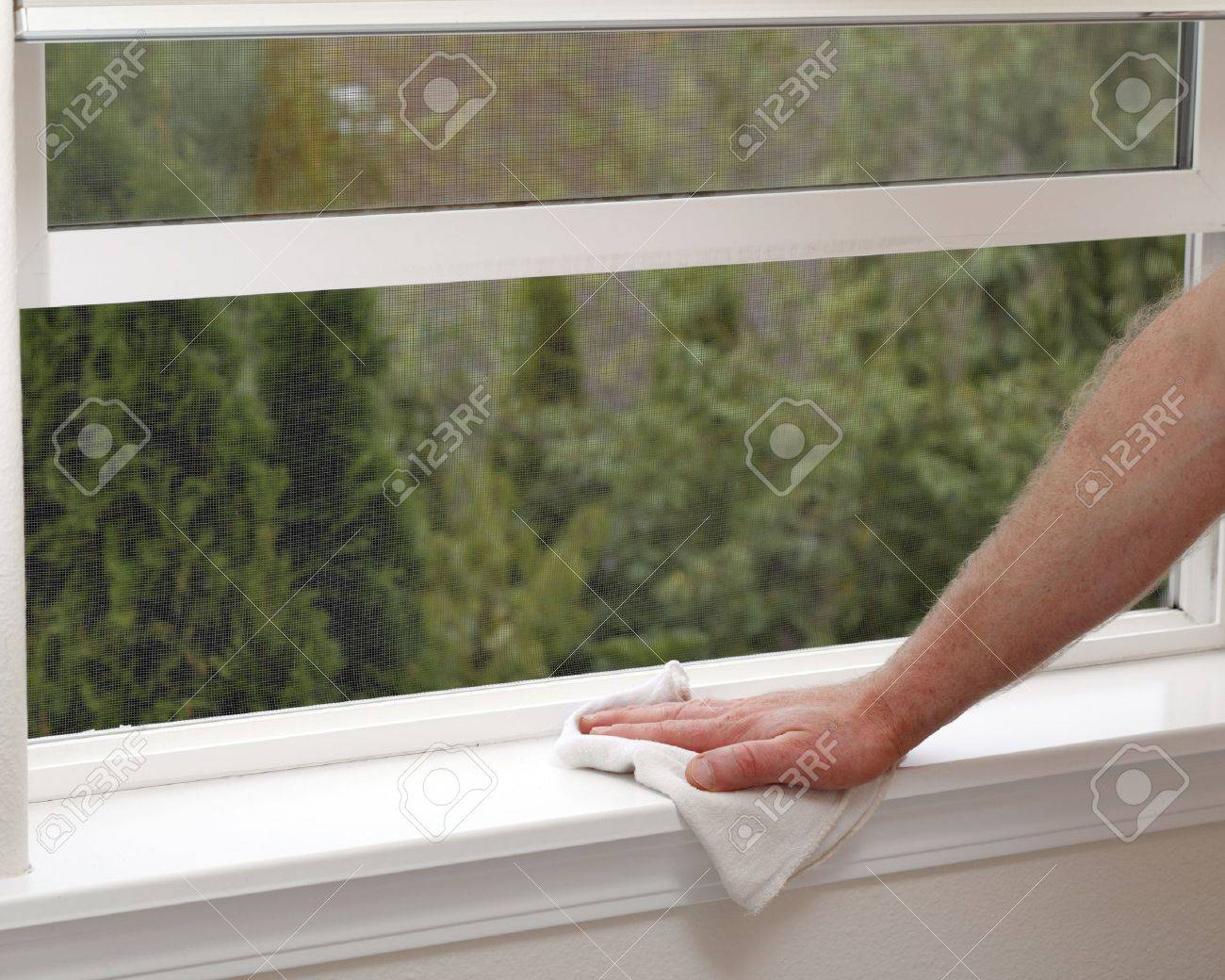 Hand dusting a window sill to reduce allergens in the home. Stock Photo - 10784672